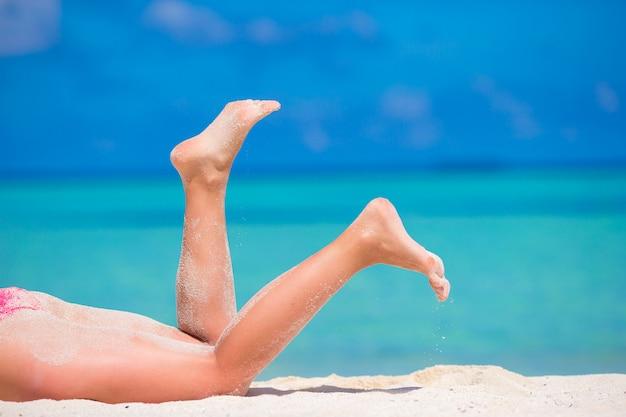 Female slim tanned legs on a white tropical beach