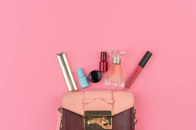 밝은 분홍색 배경에 화장품의 전체 여성 작은 핸드백