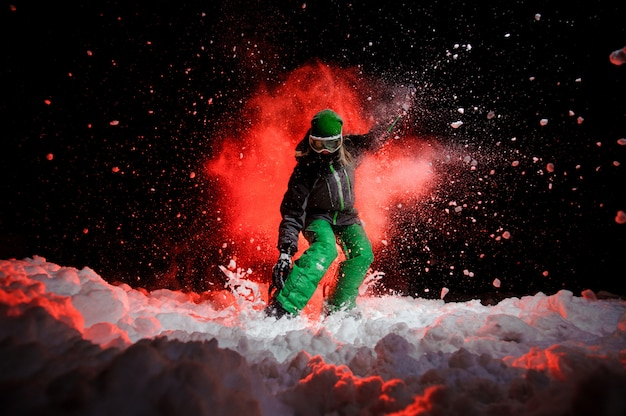 Female snowboarder dressed in a green sportswear standing on the snow slope