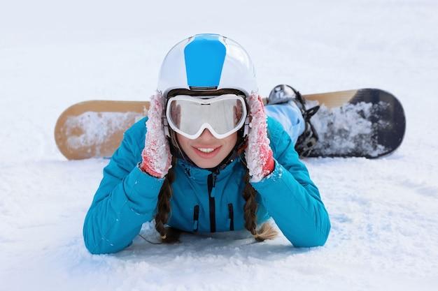 Женский сноубордист на лыжной трассе на заснеженном курорте. зимние каникулы