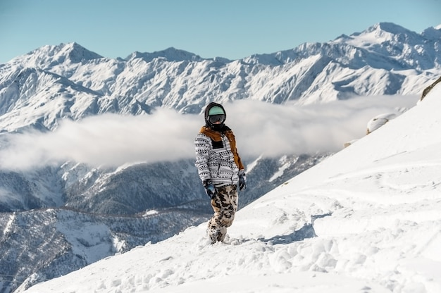 Female snowboarder in sportswear standing against the high mountain peaks