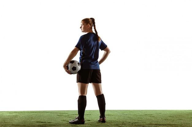 Calcio femminile, giocatore di football americano che dà dei calci alla palla, preparandosi nell'azione e moto isolato su fondo bianco