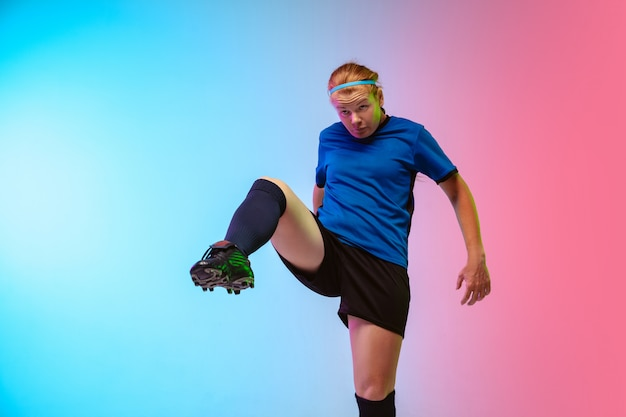 Female soccer, football player training in action isolated on gradient studio background in neon light