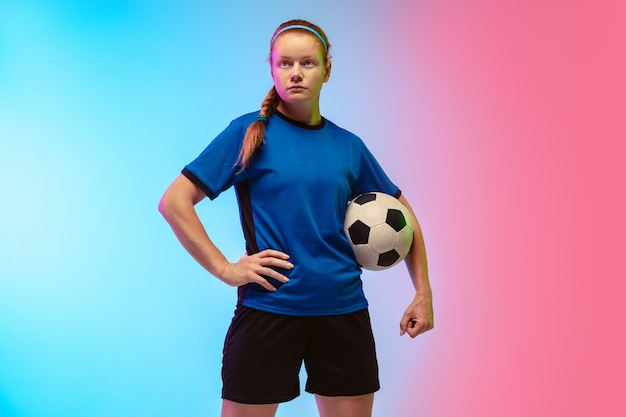 Female soccer, football player training on neon wall, youth