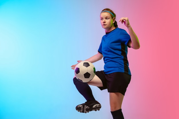 Female soccer, football player training on neon wall