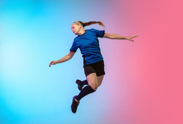Female soccer football player training on neon