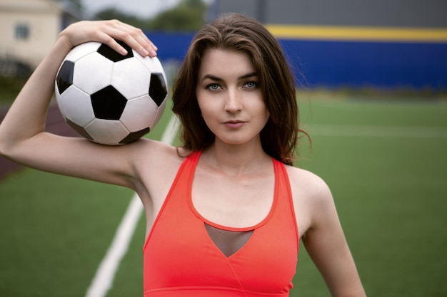 The female soccer player put the ball on her shoulder
