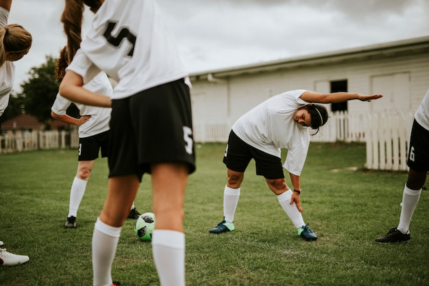Female soccer team players stretching pre game