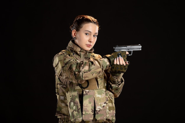 Female soldier in camouflage aiming gun on a black wall