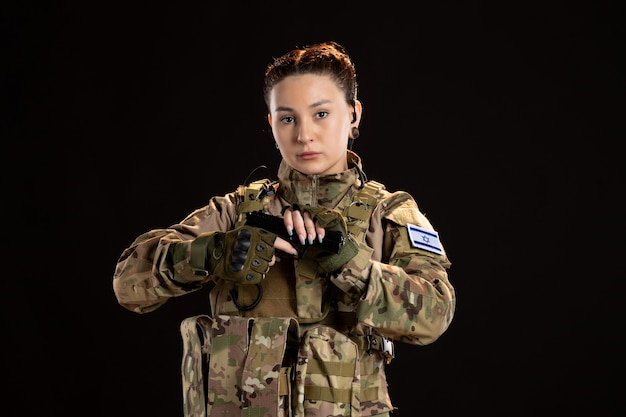 Female soldier in camouflage aiming gun on black wall