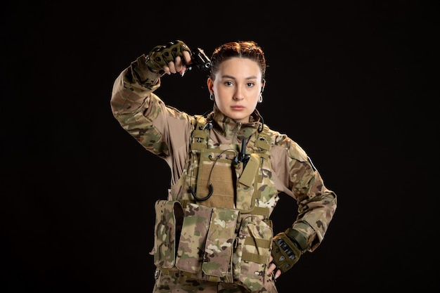 Female soldier in camouflage aiming gun on the black wall