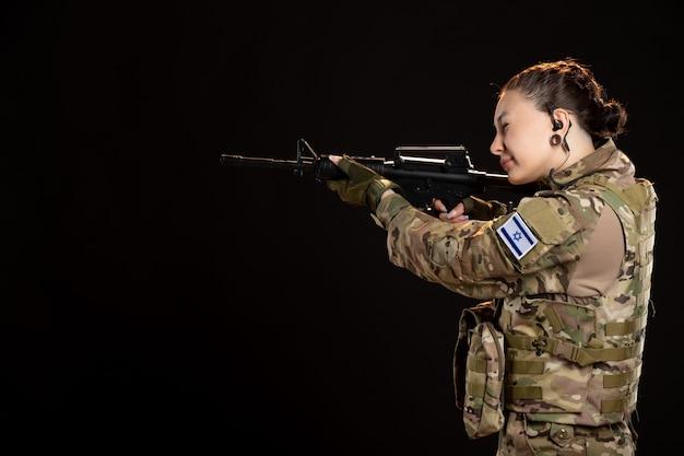 Soldato donna in mimetica che mira mitragliatrice sul muro scuro
