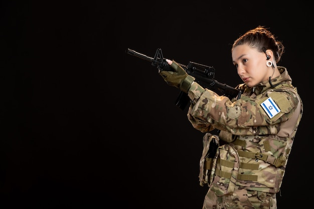 Female soldier in camouflage aiming machine gun on dark wall