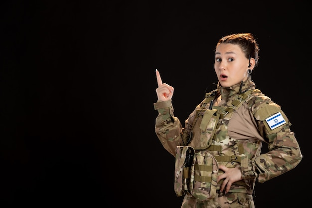 Female soldier in camouflage on a black wall