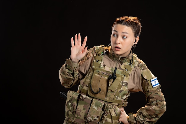 Female soldier in camouflage on black wall
