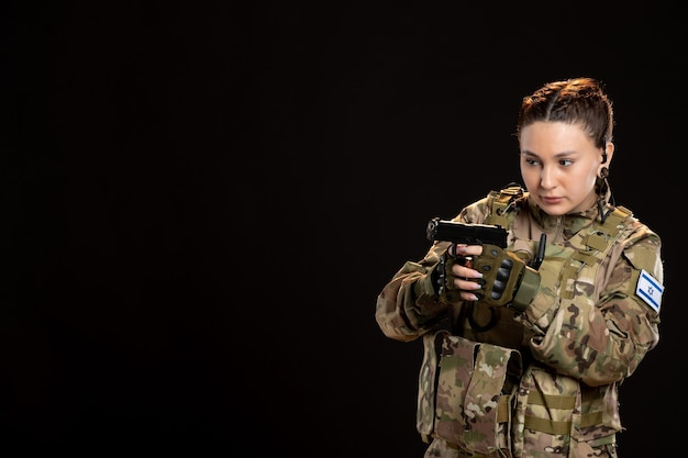 Female soldier in camouflage holding gun on black wall