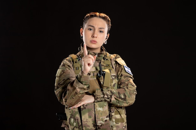 Female soldier in camouflage warns on black wall