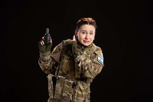 Soldato donna in mimetica con granata in mano sul muro nero