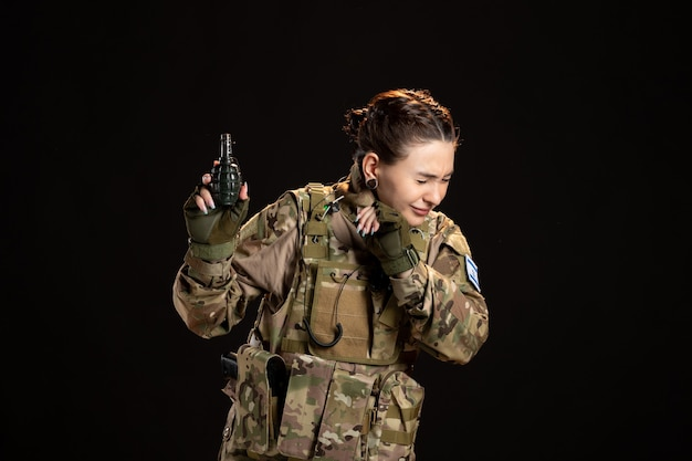 Female soldier in camouflage with grenade in her hands on black wall