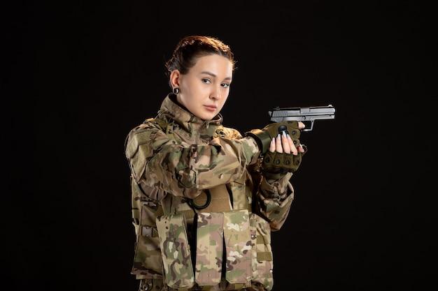 黒い壁に銃を狙う迷彩の女性兵士
