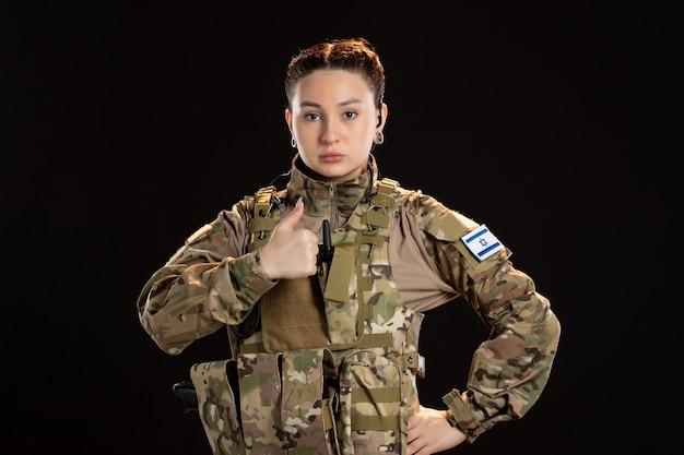 Женщина-солдат в камуфляже на черной стене