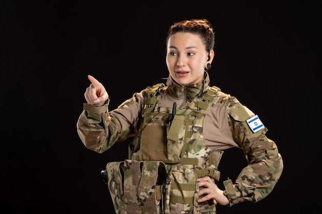 黒い壁に迷彩を着た女性兵士