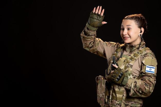 黒い壁に手榴弾を付けた迷彩の女性兵士