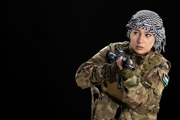 Женщина-солдат в военной форме целится из пулемета на черной стене