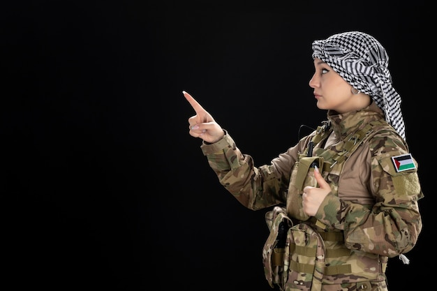 검은 벽에 군복을 입은 여성 군인