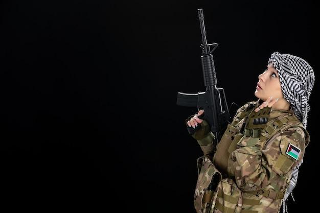 黒い壁にライフルを持つ軍服を着た女性兵士