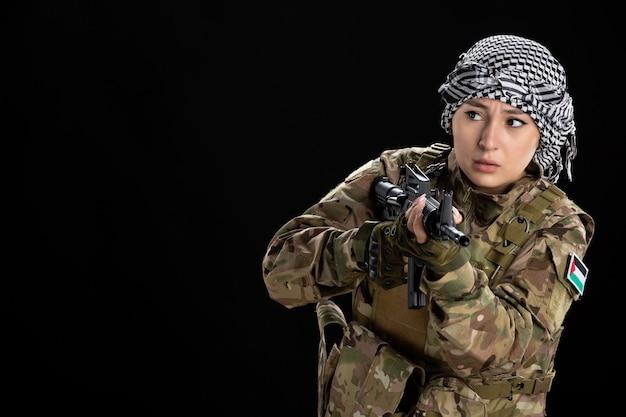 Soldato femminile in uniforme militare che mira mitragliatrice sulla parete nera
