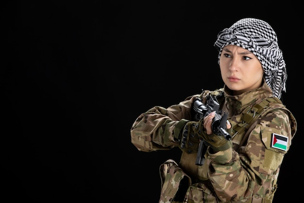 Female soldier in military uniform aiming machine gun on black wall