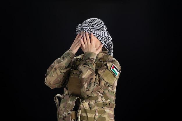 Soldato femminile in uniforme militare sul muro nero