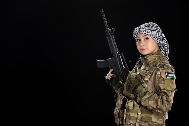 Female soldier in military uniform with rifle black wall