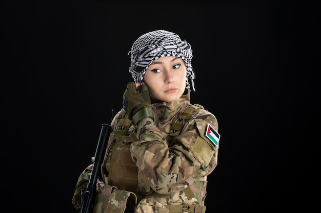 Female soldier in military uniform with rifle on a black wall