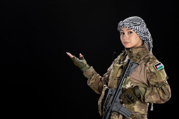 Female soldier in military uniform with rifle on black wall