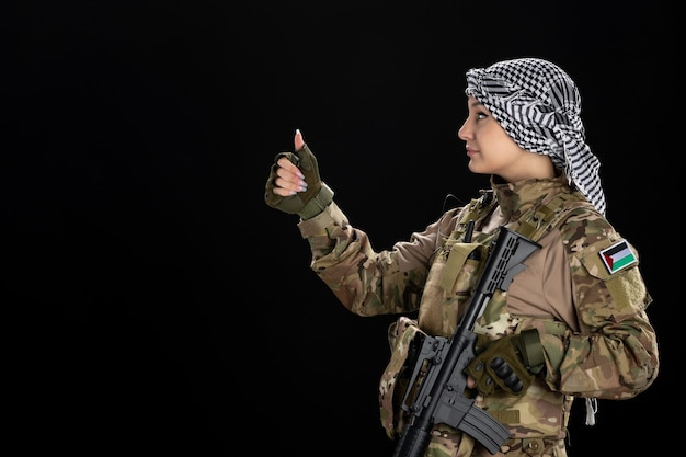 Female soldier in military uniform with rifle on the black wall