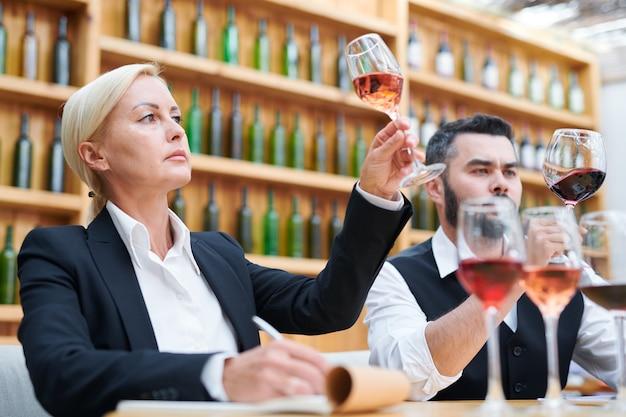 Женщина-сомелье и ее коллега в официальной одежде смотрят на вино в бокалах, исследуя его цвет на работе