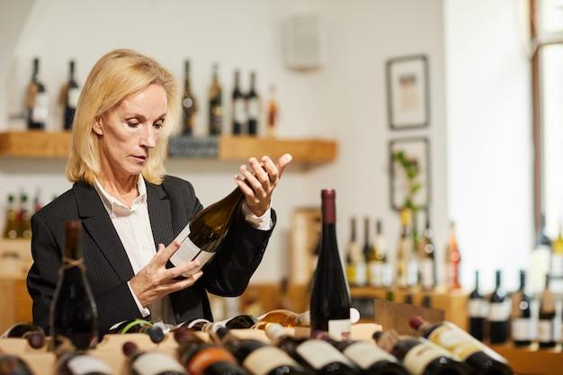 Женский сомелье выбирая вино