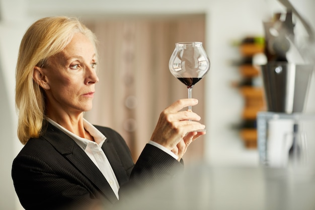 Female sommelier examining wine