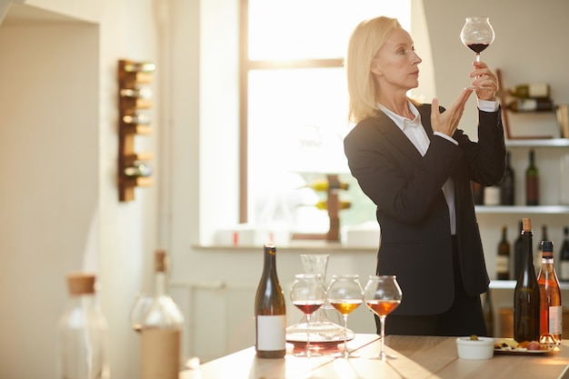 Female sommelier looking at wine