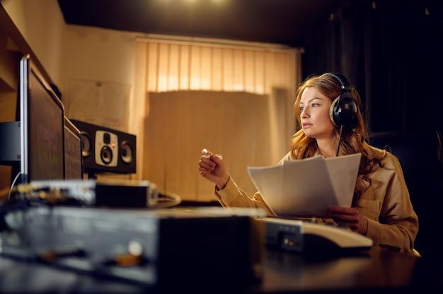 헤드폰을 끼고 스튜디오 내부를 배경으로 녹음하는 여성 사운드 엔지니어. 신디사이저 및 오디오 믹서, 음악가 작업장, 창작 과정