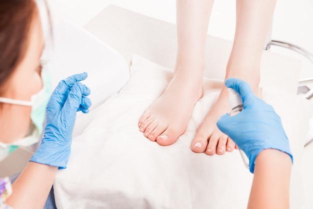 Женский спа-специалист делает педикюр женщине на специальной поверхности процедуры.