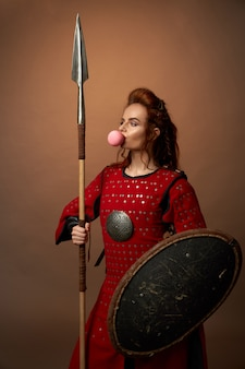 Female spartan warrior with shield and spear and chewing gum
