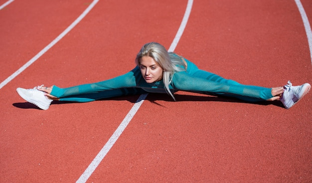 운동복을 입은 여성 스포츠 선수는 운동복을 입고 운동을 하기 전에 워밍업을 하고 스트레칭을 합니다.