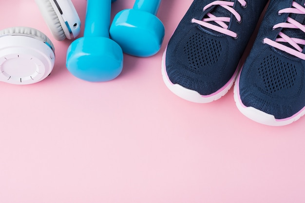 Female sport shoes, blue dumbbells andwhite headphones  with copy space, top view