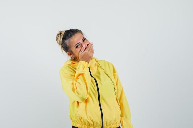 Donna in tuta sportiva tenendo la mano sulla bocca e guardando felice, vista frontale.