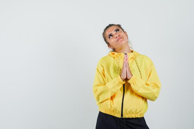 Donna in tuta sportiva che mostra il gesto di namaste e sembra speranzosa, vista frontale.