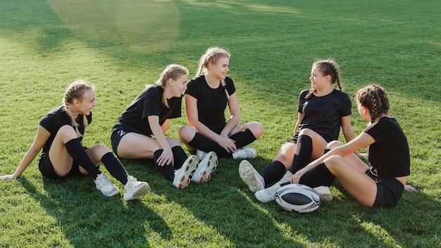 草の上に座っている女性のスポーツチーム