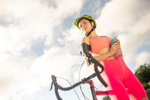 女性スポーツマン。手に水のボトルを持つ明るいスポーツウェアの若いかわいい女の子